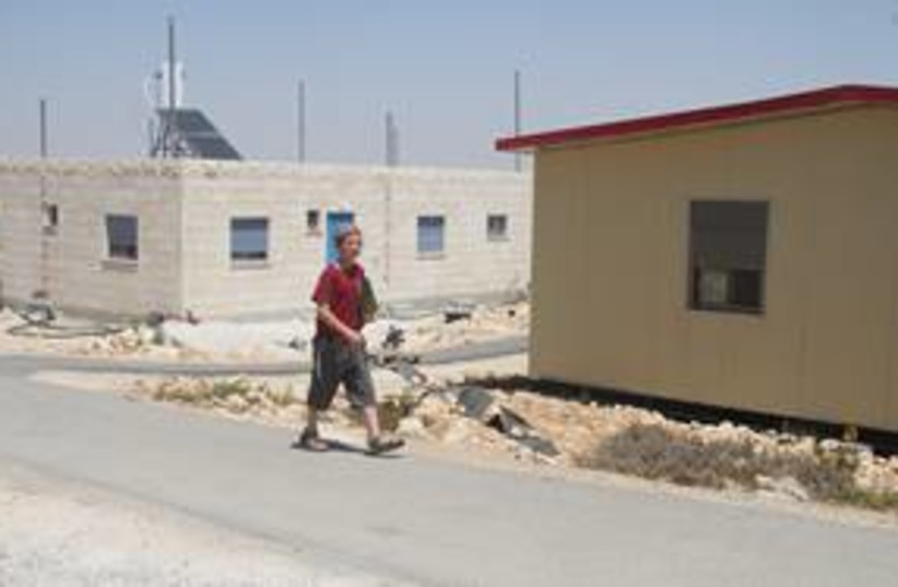 Boy walks past homes in W. Bank outpost of Migron 311 (photo credit: Tovah Lazaroff)