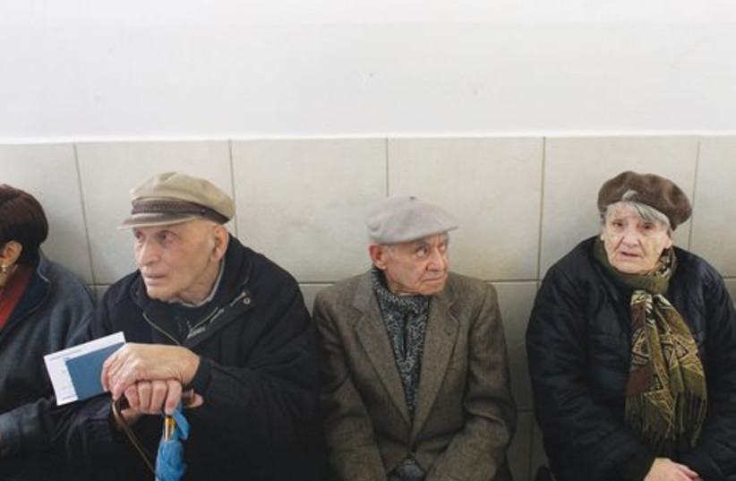 Elderly Israelis wait to vote at a polling station. (photo credit: Reuters)
