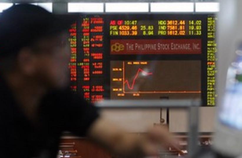 Stock trader monitors market movement 311 (R) (photo credit: REUTERS/Cheryl Ravelo)