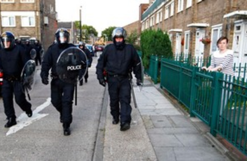 Riot police patrol through an estate in east London 311 (R) (photo credit: REUTERS/Andrew Winning )