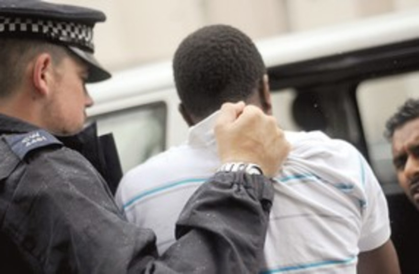 POLICE OFFICERS arrest a man in London (photo credit: REUTERS/Anthony Devlin)