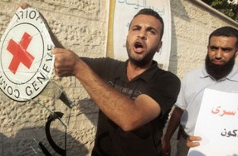 Palestinian holds IRC sign outside Hamas_311 (photo credit: Reuters)
