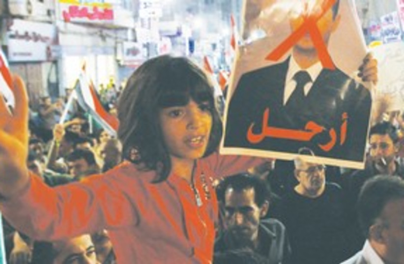 Girl holds poster of Assad311 (photo credit: Mohamad Torokman/Reuters)
