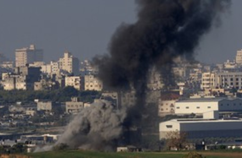 Smoke rises after an IAF airstrike in Gaza 311 (R) (photo credit: Ronen Zvulun/Reuters)
