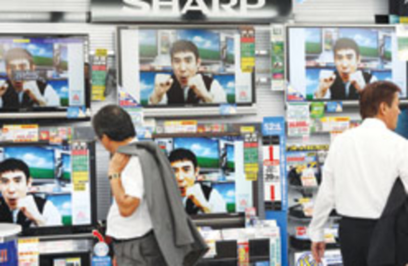 A shopper looks at Sharp flat-panel TVs at an electronics shop in Tokyo. Japan's return to growth in the second quarter marked the end of a yearlong recession. (photo credit: AP)