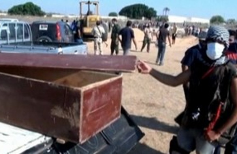 Libyan fighter displays coffin 311 (R) (photo credit: Reuters)