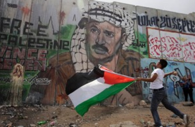 Palestinian youth throws stones at Kalandia checkpoint 311 (photo credit: REUTERS/Darren Whiteside)