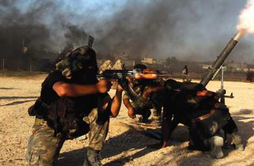 Islamic Jihad Militants launch rocket  in Gaza 521 (photo credit: Reuters / Ibraheem Abu Mustafa)
