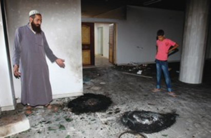 Palestinians look at burned tires in mosque 311 (photo credit: Reuters)