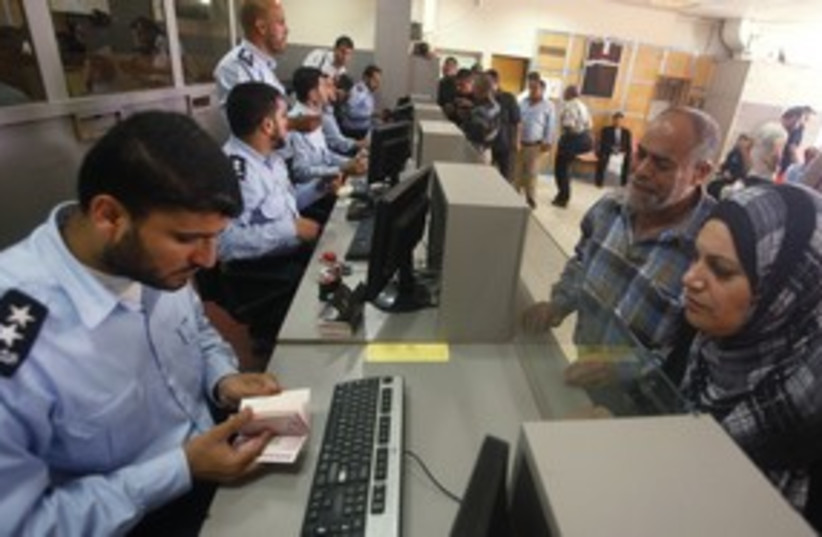 Hamas policeman checks passport at Rafah border 311 (R) (photo credit: Suhaib Salem / Reuters)