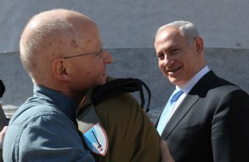 Gilad Schalit hugs father Noam, PM in background 311  (photo credit: GPO)