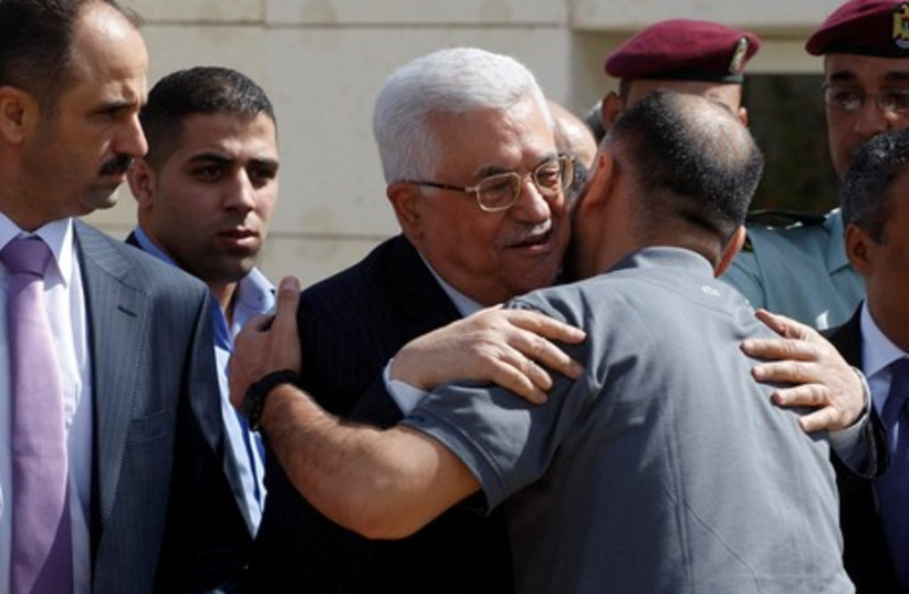 Abbas hugging newly released prisoner  R 465 (photo credit: ABED OMAR QUSINI/ REUTERS)