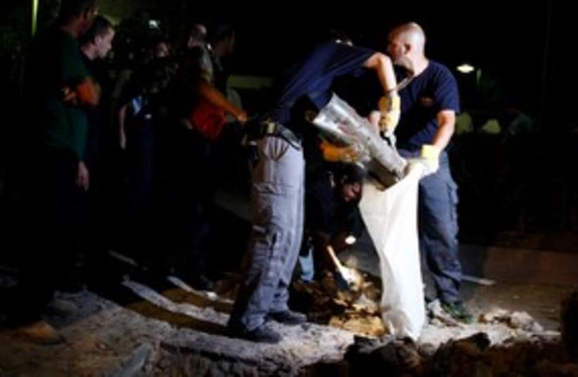 Police officiers remove the remains of a Grad rocket 311 (R) (photo credit: REUTERS/Amir Cohen)