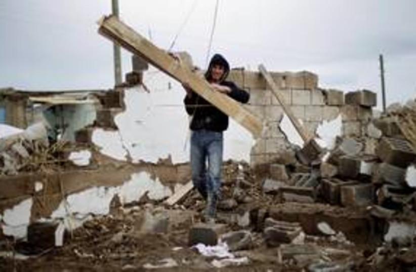 A Turkish man removes rubble after earthquake 311 (R) (photo credit: REUTERS/Morteza Nikoubazl)