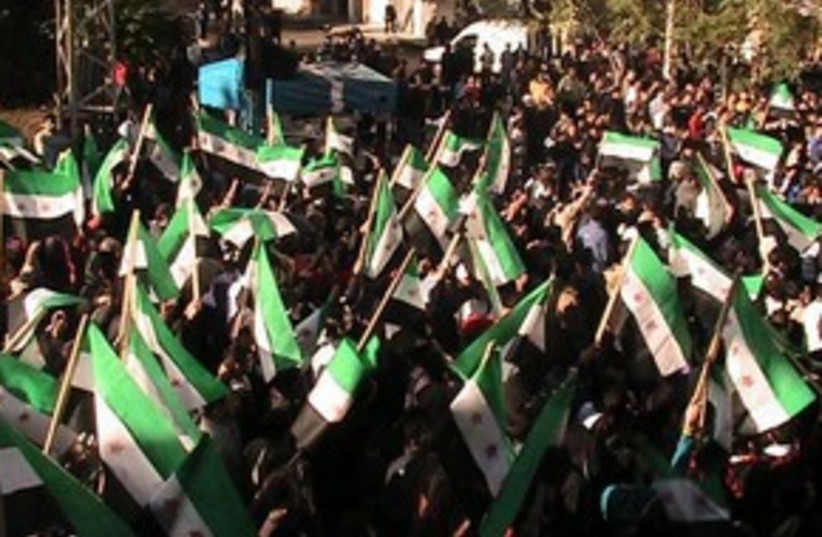 Syrian protesters with old Syrian flags 311 (R) (photo credit: REUTERS/Handout)