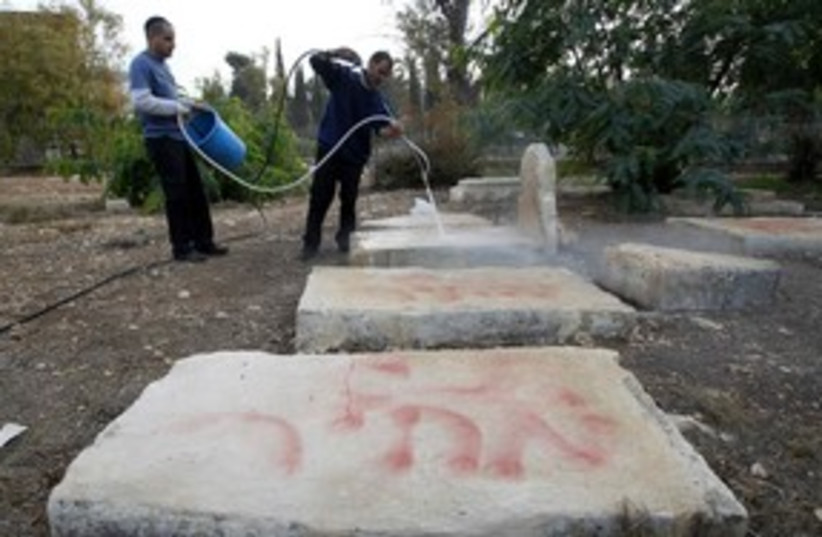 Workers clean price tag from Muslim cemetary, J'lem_311 (photo credit: Reuters)