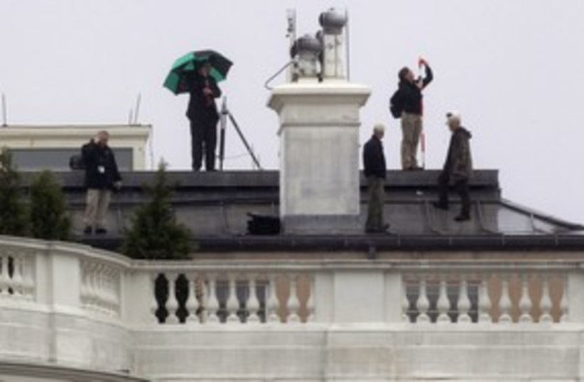 Crew atop White House where bullets hit 311 R (photo credit:  REUTERS/Kevin Lamarque)