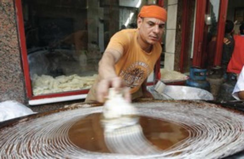 Egyptian man man prepares a traditional dessert 311 (R) (photo credit: REUTERS)