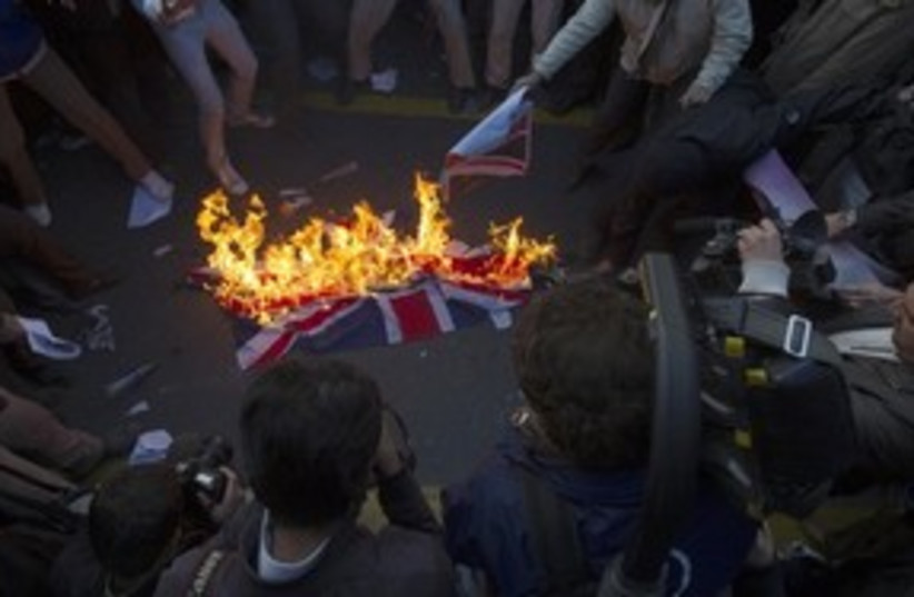 Iranian demonstrators burn British flag 311 R (photo credit: Reuters)