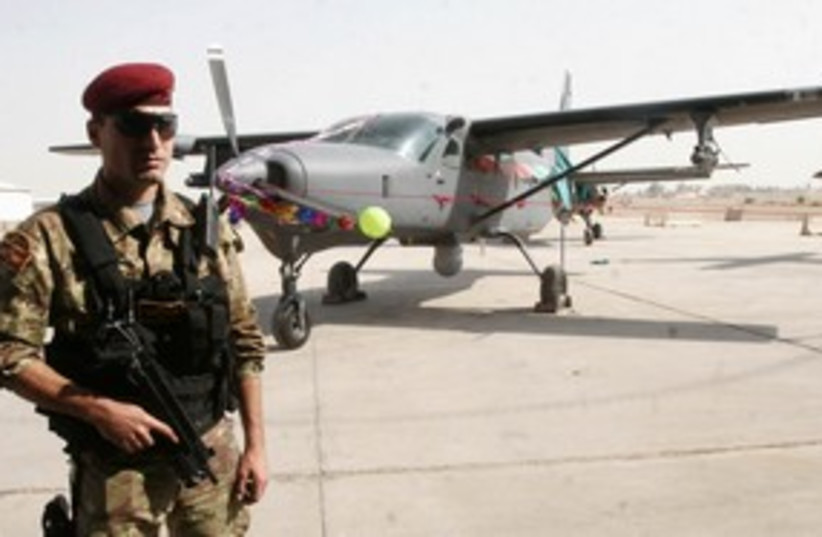 Iraqi soldier guards fighter plane 311 R (photo credit: REUTERS/STRINGER Iraq)
