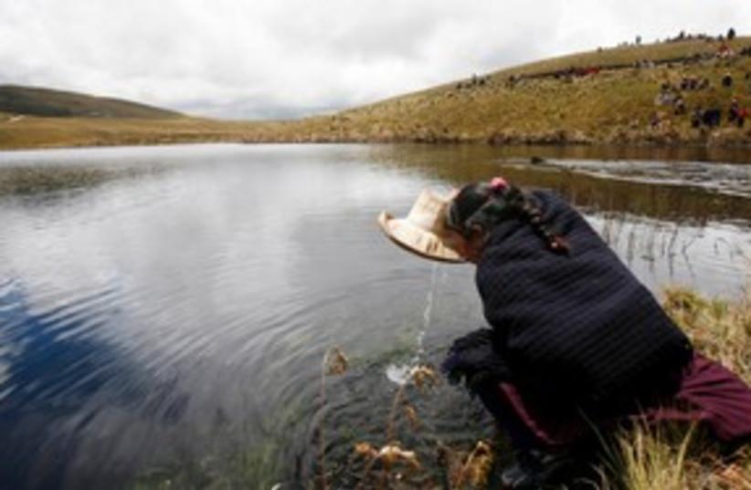 Andean woman drinks water from Cortada lagoon 311 (R) (photo credit: REUTERS/Enrique Castro-Mendivil)