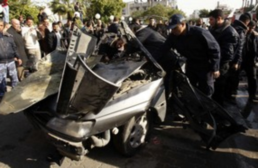 Hamas security forces survey car hit in IAF strike_311 (photo credit: Reuters/Ibraheem Abu Mustafa)
