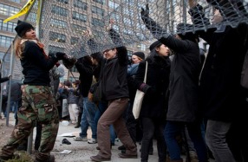 Occupy protesters lift fence in NY 311 (photo credit: REUTERS)