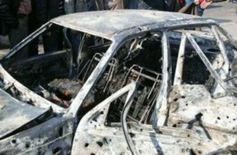 A damage car at the scene of bombings in Damascus 311 (R) (photo credit: REUTERS/ Sana/Handout )