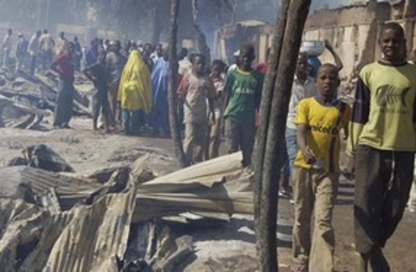 Nigerians walk by after fire razes market 311 (photo credit: REUTERS)