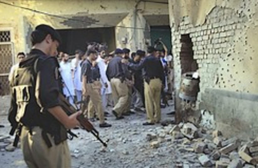 Pakistan police officers examine the site of a suicide bombing on the outskirts of Peshawar on Sunday. (photo credit: AP)