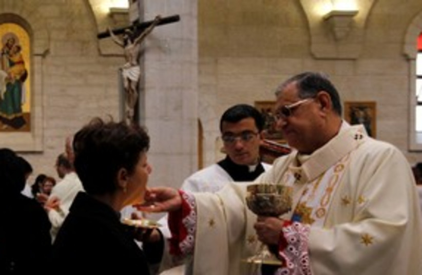Latin Patriarch Twal gives communion in Bethlehem 311 (R) (photo credit: REUTERS/Ammar Awad)