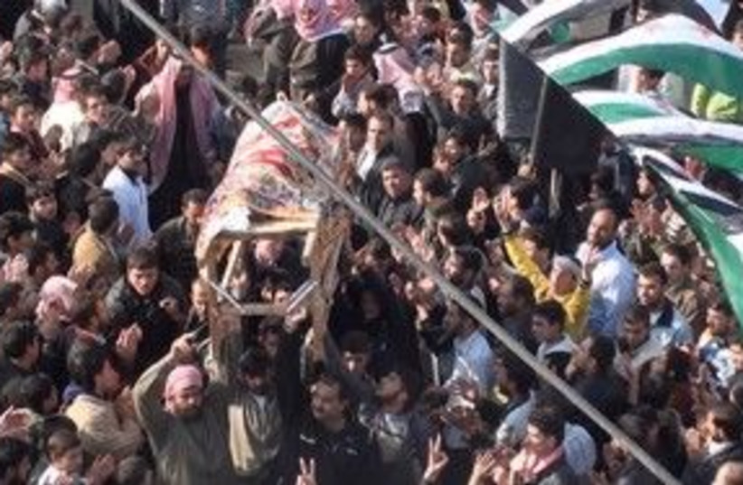 Protesters carry a coffin near Homs, Syria 311 (R) (photo credit: REUTERS/Handout)
