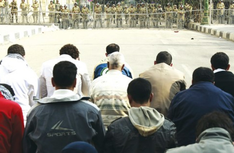 Muslims pray in front of soldiers, Egypt_521 (photo credit: Reuters)