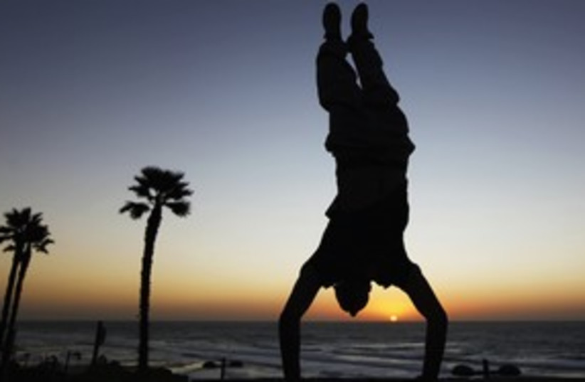 Youth does a handstand on the beach in Netanya 311 (photo credit: Reuters)