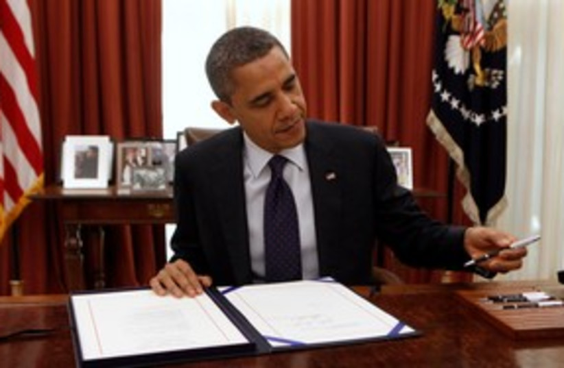 Barack Obama signing a bill 311 (R) (photo credit: REUTERS/Kevin Lamarque)