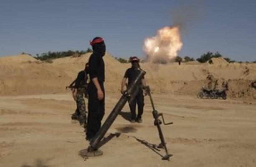 Palestinian terrorists fire a mortar shell in Gaza 311 R (photo credit: Ibraheem Abu Mustafa / Reuters)
