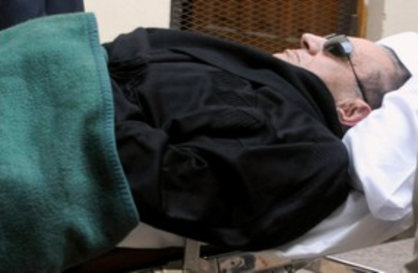 Mubarak laying down in court 311 (photo credit: REUTERS)