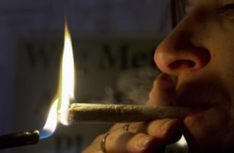 A woman smokes marijuana joint pot ganga toke 311 (R) (photo credit: Toussaint Kluiters / Reuters)