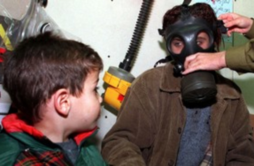 Boy watches as mom is fitted for a gas mask 311 (R) (photo credit: Jim Hollander / Reuters)