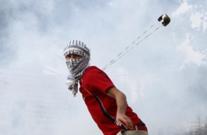 Palestinian throws a stone at West Bank demonstration 311 (R (photo credit: Mohamad Torokman / Reuters)