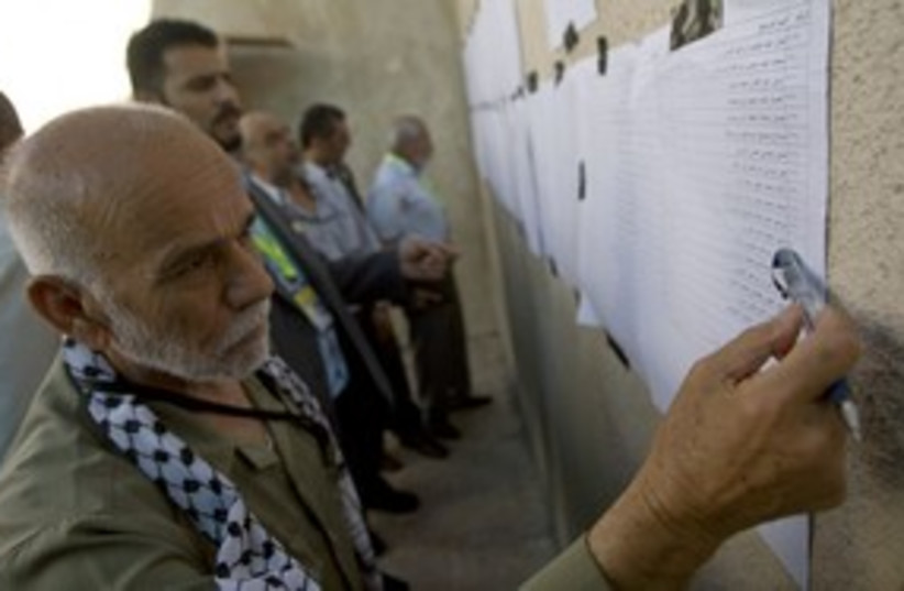 Fatah member looks at list of candidates 311 (R) (photo credit: Fadi Arouri / Reuters)