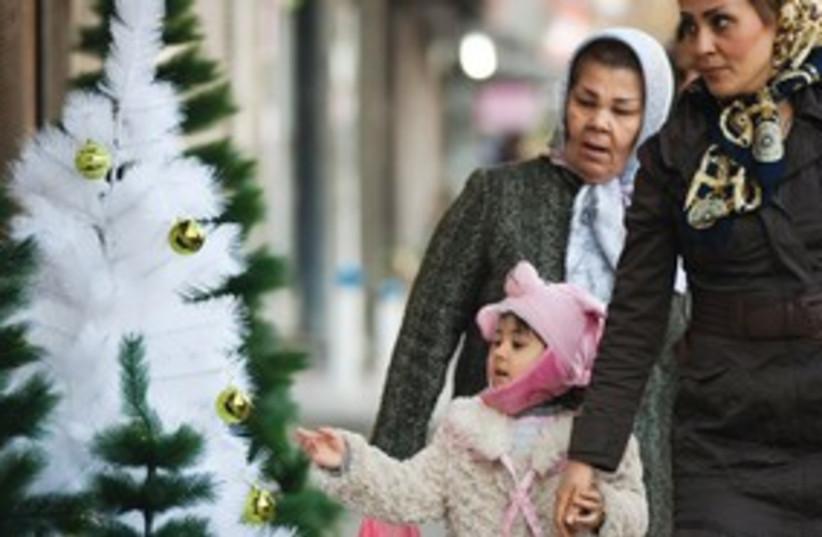 Mother, daughter look at Christmas trees in Tehran_311 (photo credit: Morteza Nikoubazi/Reuters)