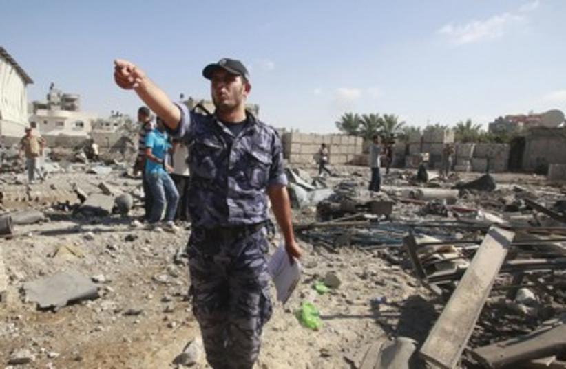 Member of Hamas security forces at site of Israeli stike 390 (photo credit: Suhaib Salem/Reuters)