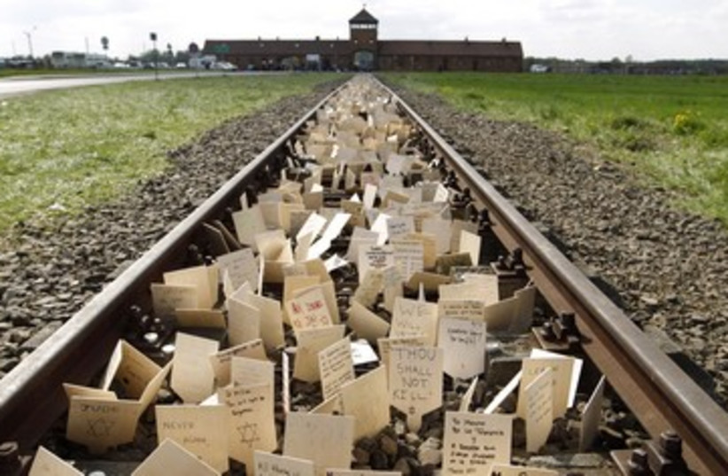 Placards placed on railway to Birkenau 390 (photo credit: REUTERS)