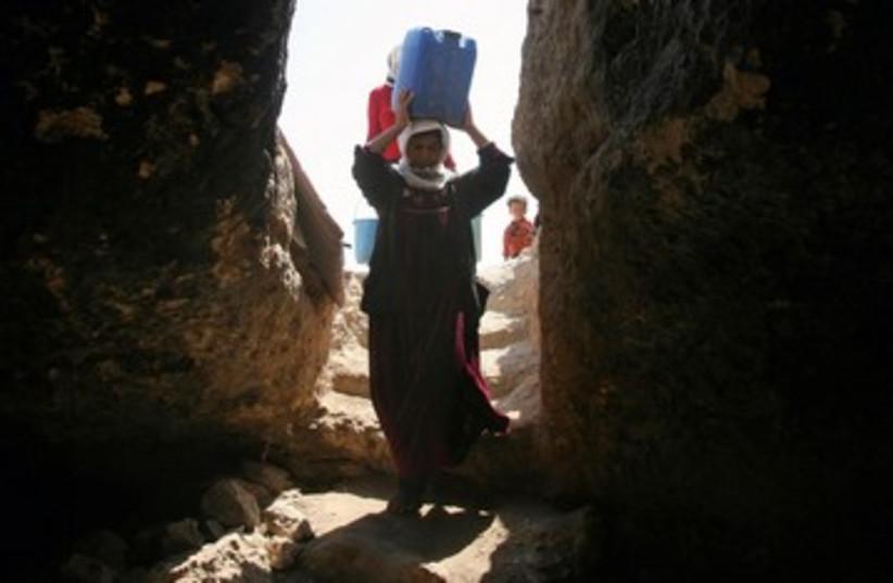 Palestinian woman carrying water 390 (R) (photo credit: Nayef Haslamoun / Reuters)