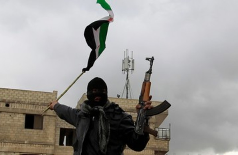 A defected Syrian soldier holds a rifle and flag 390 (R) (photo credit: REUTERS/Ahmed Jadallah )