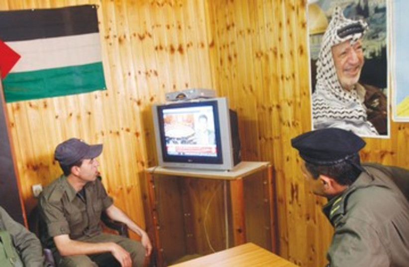 Palestinian security officers watch TV 390 (photo credit: Abed Omar Qusini/Reuters)