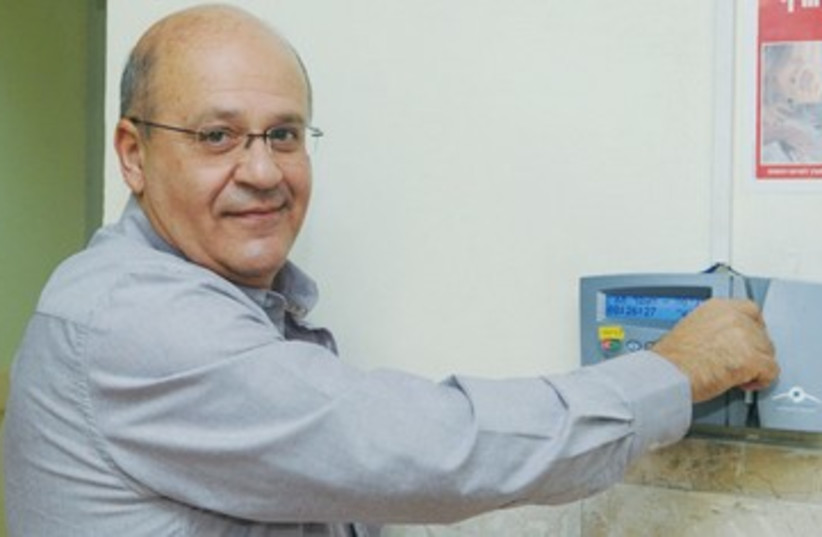 Dr Chezy Levy punches time clock 390 (photo credit: Barzilai Medical Center)