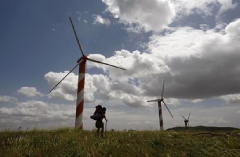 Hiker walks past wind turbines in the Golan Heights_390 (photo credit: Ronen Zvulun/Reuters)