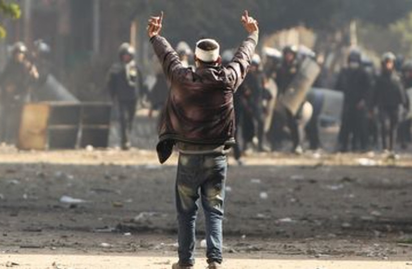 Protester gestures at police during Cairo clashes 390 (R) (photo credit: REUTERS/Suhaib Salem)